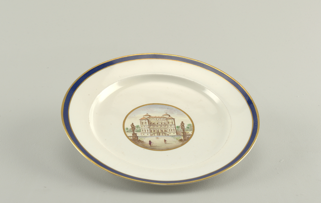 Circular plate of grayish porcelain with blue band between two gilt lines around rim; gilt-bordered circular medallion in center with polychrome ruins of Villa Borghese.