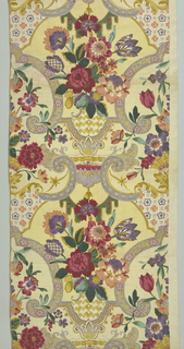 Polychrome block-print in two shades of pale yellow linen. Central motif: an urn patterned by imbricated pattern in yellow, contains brightly colored flowers -- red, purple, yellow, peach (including one checkered tulip). Urn is surrounded by grey strapwork - patterned by yellow scroll with pink flower heads. Intermittent areas of strapwork patterned by area with rows of alternating purple and peach flowers. At base of urn is an area patterned in purple net with red trim; a small green canopy below. Condition: soiled.