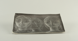 Rectangular tray of white clay, with up-turned edges.  On dark gray ground, underglaze sgraffito decoration of three female heads.