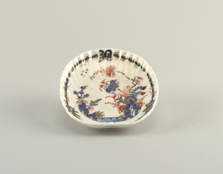 Molded scalopped shell form with Chinese-style decorations and bow knot.