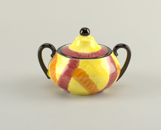 Circular body narrowing slightly at the top with two c-shaped handles on either side.  Top edge and handles painted black.  Yellow background with connected, irregular stripes of orange and burgundy.   Conical lid with black finial.  Lid is also yellow, with black edge and a bordering stripe of burgundy.