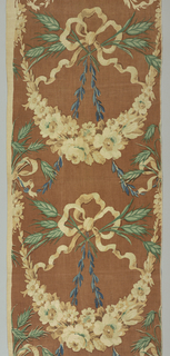 Blue, green and tan block print on brown linen. Large swag of tan flowers. Above swag is a 3-looped bow of tan ribbon with sprays of green wheat through the loops. Two blue leaf stalks hang from bowknot.