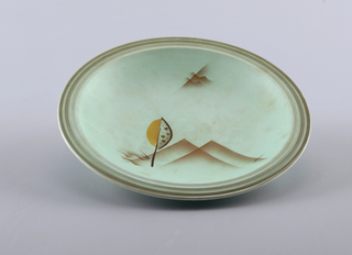 Deep circular concave dish on raised bottom rim with a horizontally grooved top edge.  Turquoise ground with airbrushed brown on the edge.  Design in center of airbrushed brown overlapping right angles, wavy brown lines, darker brown slashes, and an abstract oval form of brown dots and orange with a dark brown line coming out of it.