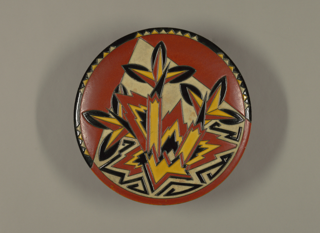 Circular, slightly concave form featuring overall abstract, variously intersecting, jagged-edged design from which extend plant-like motifs in orange, yellow, black and off-white, all superimposed on large off-white triangle, with orange ground color in background; upper part of charger's perimeter features alternating yellow and off-white series of saw-tooth pattern that wraps approximately halfway around form; all edges of motifs raised and outlined in black, giving a slightly more 3-dimensional quality to overall design; all colors are slightly mottled in appearance; underside glazed in black.