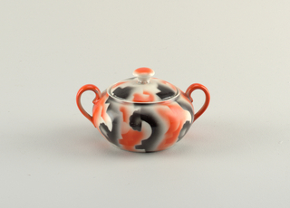 Sugar bowl with atomized red and black glaze in amorphous design on a white ground.