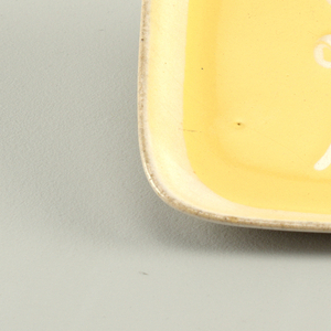 Square in shape, yellow glaze with lighter border around rim and stylized flower/foliage motif.