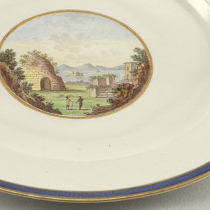 Plate with blue and gold border. At center of well, depiction of two figures in Roman ruins landscape with sea in background.