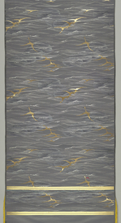 Dark gray satin ground closely crossed with silver linear wave conventions with medium-scale repeat (upright in first row, reversed in alternate row) of golden geese in flight with spread wings crossing a darker gray cloud. Two wide plain satin selvages. Two pair of gold bands across the top and bottom of panel. Bright yellow cotton cloth strip tacked to top end.