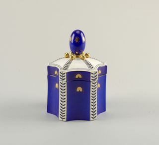 Hexagonal box and domed lid with egg-shaped finial. Cobalt glaze panels separated by vertical stripes with black leaf motif. Gilded details.