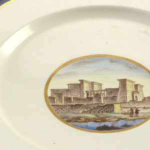 Circular plate of grayish porcelain with blue band between two gilt lines around rim; gilt-bordered circular medallion in center with polychrome ruins of Tempio dell'Isola di File.