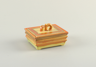 Rectangular box widening at mouth sitting on four squat feet and groove-stepped sides.  Yellowish ground with drippy orange and brown lining the grooves.  Rectangular sunken-in lid with an orange and brown lopping finial.  Also a yellowish ground with lines of orange, tan, and brown on the edge.