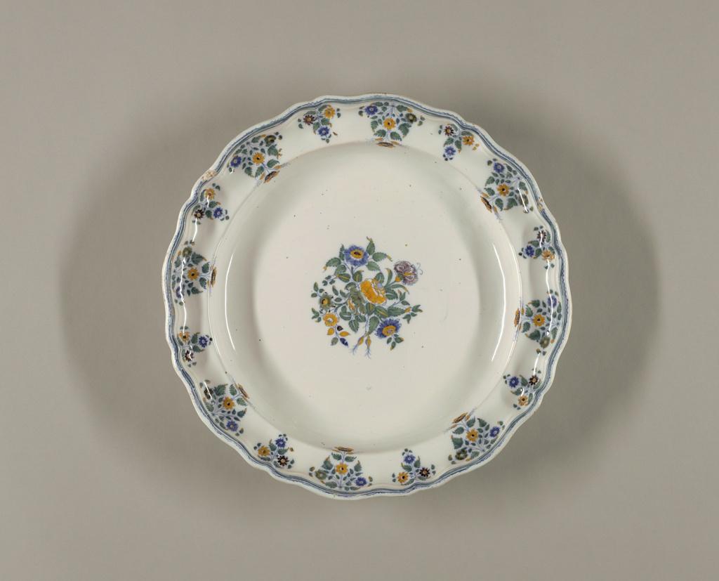 """Shaped rim with blue bands, fleur de pomme de terre (""""potato flower""""), and central bouquet medallion."""