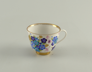 Cup has straight flaring sides, loop handle; painted with blue and gilded flowers. Saucer is circular, painted with wide border of similar blue and gilded flowers.