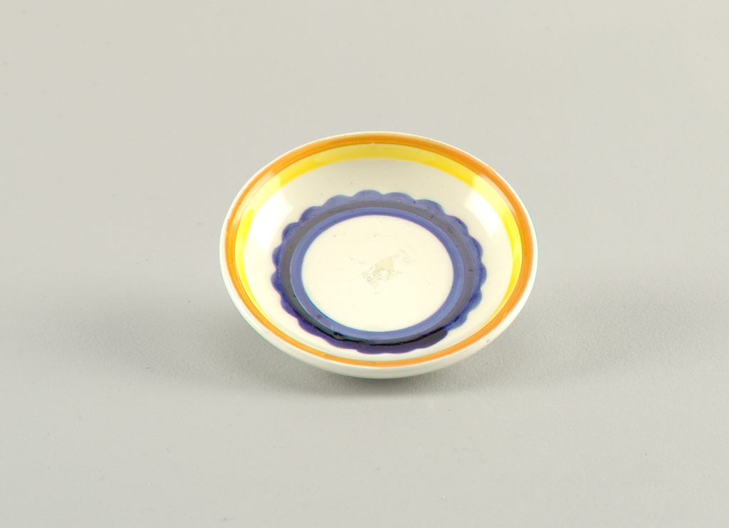 Circular concave dish.  Cream background with concentric circles from edge to center of: orange, yellow, cream, royal blue with a scalloped edge, dark blue, royal blue, a finally a round cream center.