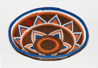 Concave shallow bowl woven of plastic coated telephone wires, over a heavy wire frame. Colors: brown, white, orange, red, blue. Decoration arranged in bands encircling bowl, with stripes and upright triangles of blue, white and orange against brown ground. Center with concentric bands of brown and orange. One side further ornamented with red lozenge shape in upper register. Outside of bowl duplicates interior patterns.