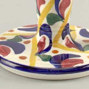 Bowl with lip on a high, conical stem and wide circular base. All painted with broad strokes in primary colors and green. Tall unpainted handle.