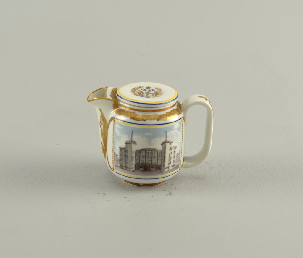 Cylindrical, rounded at base and top, curved spout, wide loop handle, disk-shaped lid; painted in polychrome enamel on front with picture of the Gorky Palace of Culture and on back a griffin from Bankovsky Bridge in gilding; gilded ornament of ribbon border around top of body, flags along sides of spout, emblem on lid, on handle.