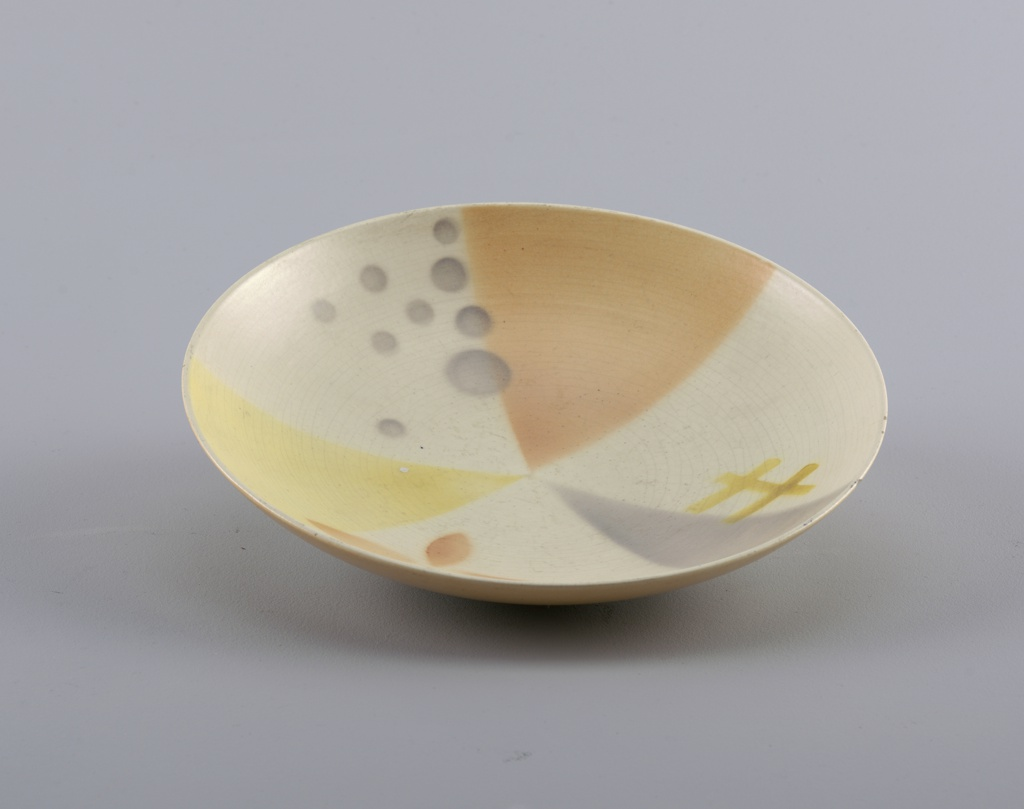 Round bowl with pale peach, grey and yellow triangles with small circles.