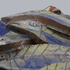 Irregular round plaque with five stylized fish shapes mounted overlapping each other.  A hanging wire runs through the top curve of the hanging.  Top of plaque glazed with a mottled blue.  Brown clay revealed on the edges.  Fish cut from thick slabs with molded eyes, black striping for scales, and splashes of blue, orange, gray, and yellow.