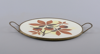 Flat circular form surrounded by thin metal rim with two handles; the white to yellow ground with brown and orange decoration of flowering horse chestnuts.   Paper label on underside.