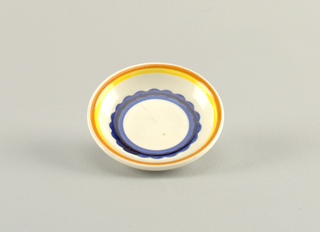Circular concave dish.  Cream background with concentric circles from edge of: orange, yellow, cream, royal blue with a scalloped edge, dark blue, royal blue, and finally a solid round cream center.