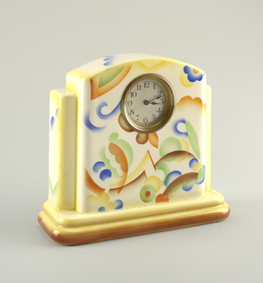 Large clock with a flat back.  Central area as a rectangle with curving top edge containing the round brass-faced clock and abstract airbrushed decoration in orange, brown, blue, green, and yellow on a cream ground.  Two tall thin rectangles brace either side with a cream ground edged in yellow.  All leads to a two-stepped cream rectangular base with yellow and brown airbrushed highlights.  Two circular holes in the bottom of the base.