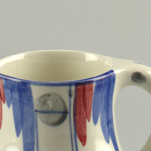 Pitcher with blue and red glaze at rim. Thin black dots at handle.
