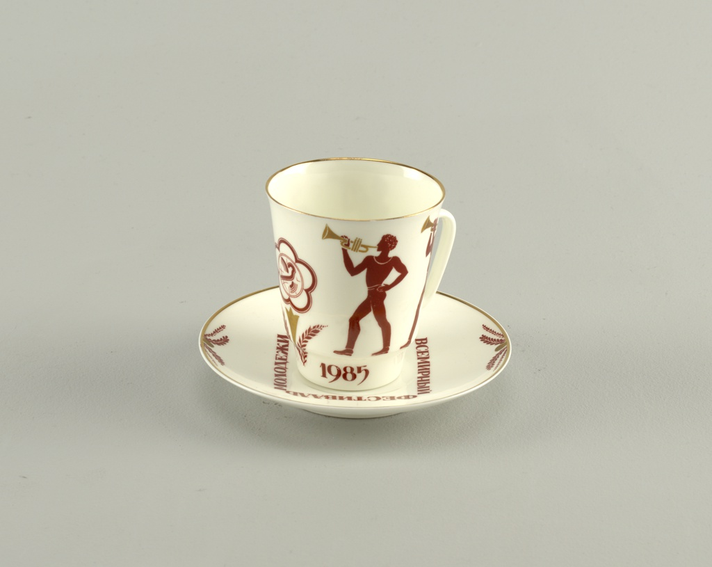"Cup cylindrical, flaring towards top, narrowed at base, loop handle; painted in orange/brown with figures of young athletes blowing trumpets, emblem, ""1985"" at base. Saucer circular; four sprays of leaves at border and inscription in square around center (in Russian): ""World Festival of Youth and Students"" painted in orange/brown, gilded band at rim."