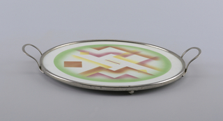Flat circular plate with abstract atomized decoration in pink, green, orange and yellow, showing chevron forms. Simple rim and handles.