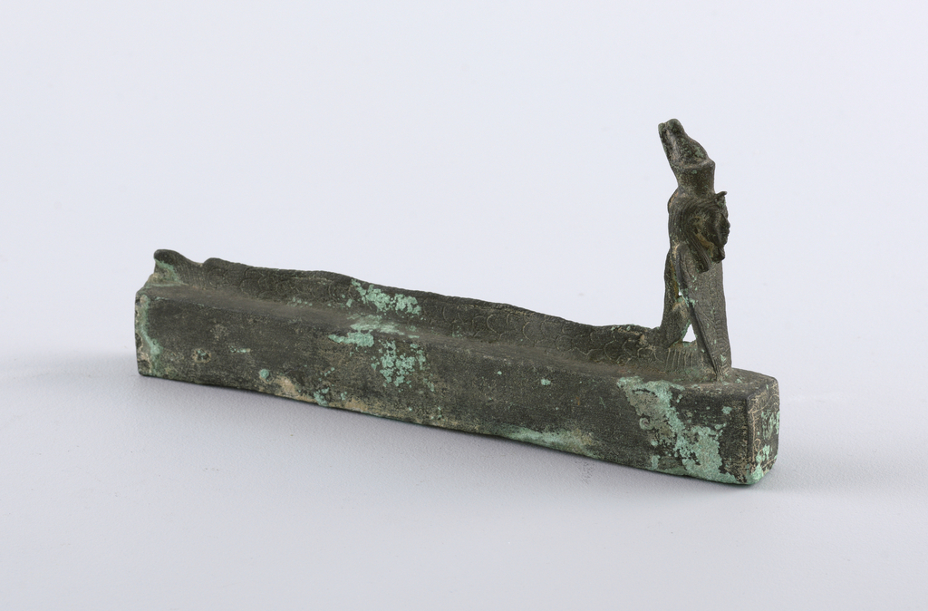 Long case surmounted by the figure of a serpent with a crowned human head.  This acted as a coffin for the god Amun in the form of an eel.