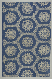 White pattern on blue background of a floral stripe creating an hexagonal grid framing 8-pointed medallions. Printing goes over edge of fabric on one side.