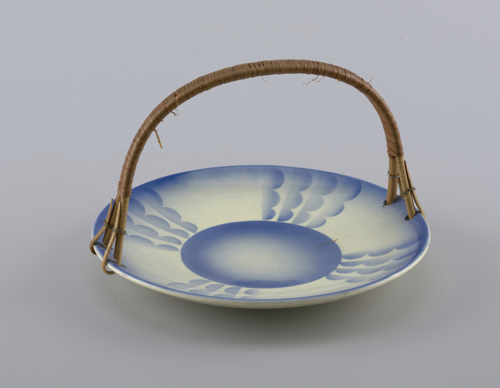 """Circular concave dish with raised bottom rim.  Four holes on edge that connect rattan semicircular handle with metal rings.  Cream background with surface decoration all in airbrushed blue.  Blue lines the edge.  Centered circle """"connected"""" to edge by four bands of four lines of three connected semicircles resembling clouds all facing clock-wise.  Plate divided into quarters by these motifs."""