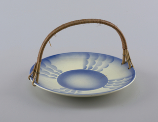 "Circular concave dish with raised bottom rim.  Four holes on edge that connect rattan semicircular handle with metal rings.  Cream background with surface decoration all in airbrushed blue.  Blue lines the edge.  Centered circle ""connected"" to edge by four bands of four lines of three connected semicircles resembling clouds all facing clock-wise.  Plate divided into quarters by these motifs."