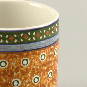 Squat cylindrical form. Interior glazed white.  Exterior decorated in four bands.  Top band with green background and white and orange stylized blossoms.  Next, a solid band of blue.  Then, the third and widest band of spongy brown with white and green circles.  Finally, a band of royal blue with stylized blossoms of white and orange.