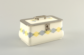 Rectangular box, swelling at bottom. Flat lid with rounding metal rim. White ground with blue and yellow diamond pattern.