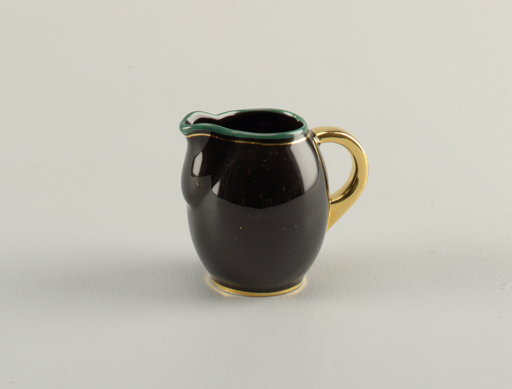 Round black creamer with gold foot and handle; mouth in turquoise and gold with slightly bulging spout.