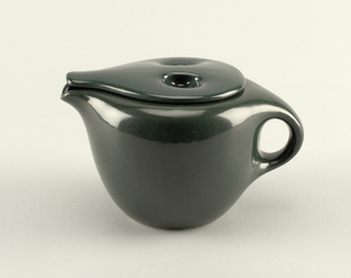Black teapot with curved sides, handle and spout. Lid with indention for finial and spout that echoes teapot spout.