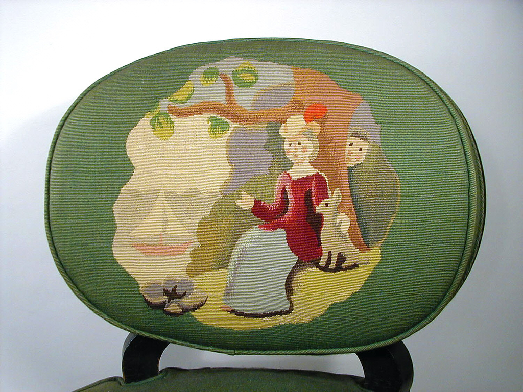 Chair with slightly curved wooden legs; round seat and back upholstered in green fabric. Seat decorated with single white flower and tan zigzag pattern; back depicts scene of a couple seated together in a forested landscape with water to the right. A small tree grows before them out of a purple bush.