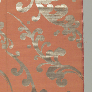 Metallic silver scrolling leaves and scattered dots alternating up the length of the salmon-colored ground. Two side-by-side repeats for continuous vertical pattern. Border at one end of fabric only of a double band of metal enclosing section of scrolling band pattern.