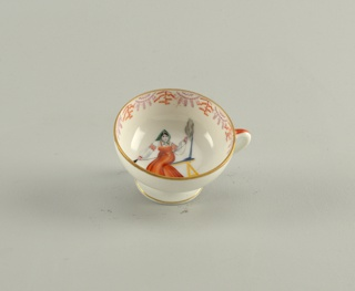 Cup with shallow bowl on raised foot, loop handle. Painted in interior of bowl with woman dressed in peasant costume, spinning with distaff; stylized border upper edge, thin gilded bands top and bottom edge of outside. Saucer round, slightly raised towards edges; painted with matching stylized border around center, two thin gilded bands bordering.