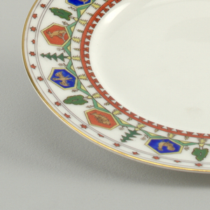 Dessert plate with straight, flat marly decorated with seven red and seven blue hexagonal cartouches with animals.  Between the cartouches green trees, above red stars and below, yellow trees and a red line with dents.