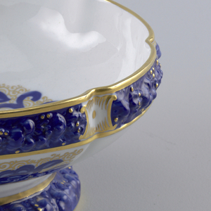 Round bowl on a spreading foot. Molded floral surface decoration glazed blue. Gilded bands and scrolling forms.