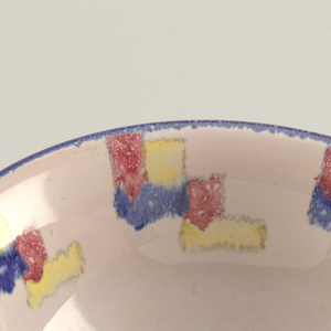 White, basic shape bowl with squares of blue, red and yellow on the inside. The outside rim has a thin stripe of blue. The body is white with a yellow stripe in the center followed by a white and then red and blue at the base. It is supported by three small feet that are colored yellow, red and blue.