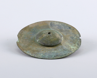 Circular form with raised dome, small hole in center.  Green patina.