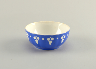 Circular deep bowl with a scalloped edge leading down to a molded undulating exterior surface.  Interior and exterior glazed white.  Royal blue covers entire exterior except for white repeating motifs of alternating single circles and stylized bunches of grapes placed near the top edge.