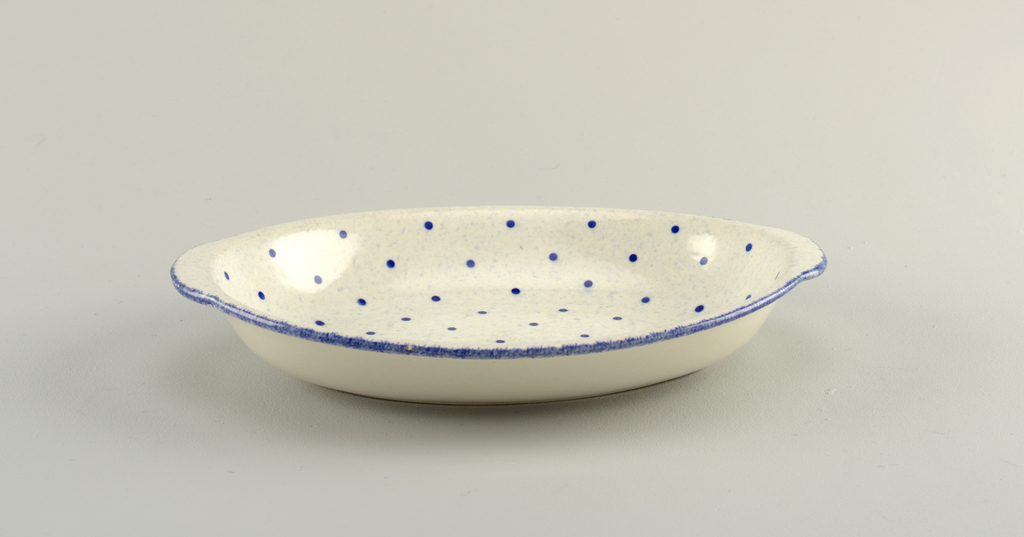 white dish with a dark blue rim and blue polka dots across the rest of the interior.