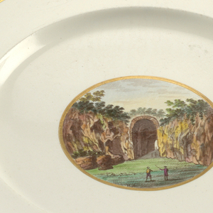 Circular plate of grayish porcelain with blue band between two gilt lines around rim; gilt-bordered circular medallion in center with polychrome landscape of rock formation of arch.