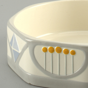 White, octagon shape dish with alternating patterns of yellow dots and blue triangles.