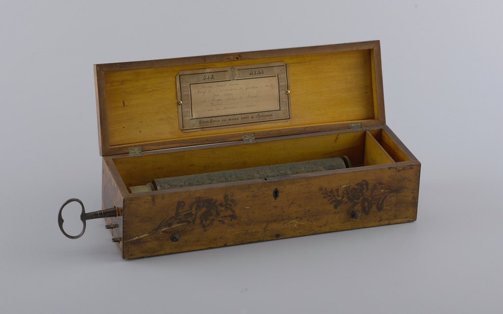 Wood box with lid attached with three hinges. At front, decoration of two roses, and a keyhole. At side, a key with the mark: IP. IG. Inside is the music cylinder. Printed paper label affixed inside the lid with two brass tacks. Striped border with lyre and face. Text reads: Six Airs / Etouffoirs en acier soit a Spiraux. Listed at center are the songs: Home Sweet Home; Motif de l'Ouverture de Gustave, d'Auber; Jim Crow; Berger Galop de Strauss; Isabel; and Finale du Serment, d'Auber.