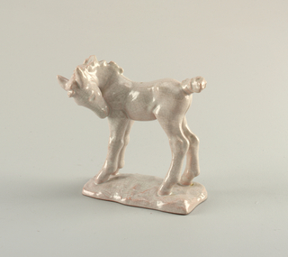 Figure of a colt with head cast down and tail up, standing on a craggy base.  Entire surface with a crackle glaze in a pinkish hue.